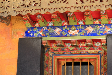 gelugpa: Manycolored painted wooden door frame under colorist roof eaves. Drepung-Rice Heap monastery of Gelugpa-Yellow Hat order at the foot of mount Ghephel. Lhasa prefecture-Tibet A.R.-China.