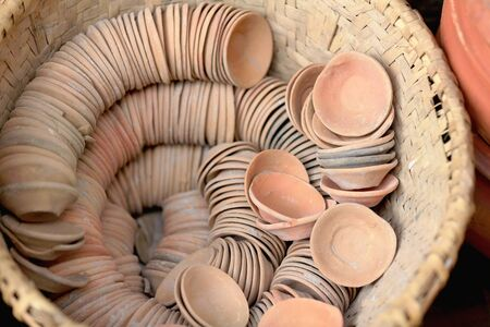 shop for animals: Set of small terracotta bowls placed in a spiral row in a wicker basket on the outside of a local handicrafts shop in the old city area. Panauti-Kavrepalanchok dstr.-Bagmati zone-Nepal. Stock Photo