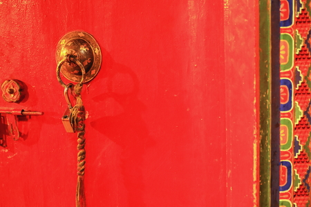 Red painted wooden door with gilded brass doorknob-braided cloth hanging and open padlock with colorist door frame
