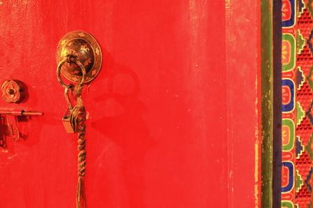 gelugpa: Red painted wooden door with gilded brass doorknob-braided cloth hanging and open padlock with colorist door frame