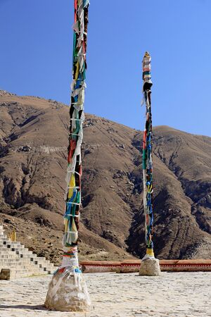 flagpoles: Wooden flagpoles with tied buddhist prayer flags in the square