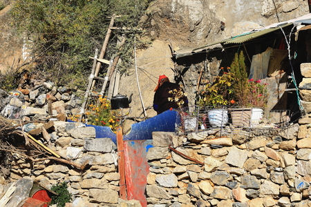gelugpa: DREPUNG, TIBET, CHINA - OCTOBER 19: Tibetan buddhist nun prepares tea in a metallic teapot on the outside of her hut in the Drepung monastery area on October 19, 2012 in Lhasa pref.-Tibet A.R.-China.
