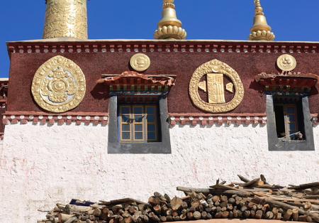 white washed: Firewood piled beside the white washed wall-gilded dhvaja or victory banner rooftopped-reddish skirt boarded with golden roundels of the Drepung-Rice Heap buddhist monastery Stock Photo