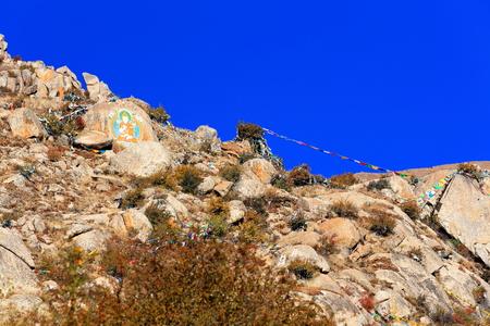 gelugpa: Tibetan buddhist prayer flags and painting on mani stone -om mani padme hum-. Drepung-Rice heap monastery of the Gelugpa-Yellow Hat order at the foot of mt.Ghephel. Lhasa pref.-Tibet A.R.-China.