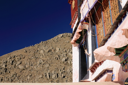 gelugpa: Colorist wooden windows under fabric edgings-gilded roundel on the red skirt board of the white washed walls of the Drepung-Rice heap buddhist monastery of the Gelugpa-Yellow Hat School at the foot of mount Ghephel. Lhasa pref.-Tibet A.R.-China. Stock Photo