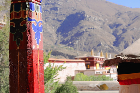 lacquerware: Red painted wooden pillars with colorist drawings-view over the roofs to the mountain. Drepung-Rice Heap monastery of Gelugpa-Yellow Hat order at the foot of mt.Ghephel. Lhasa pref.-Tibet A.R.-China. Stock Photo