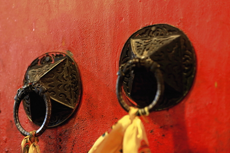 gelugpa: Red painted wooden door with doorknobs-cloths hanging from rings. Drepung-Rice Heap monastery of Gelugpa-Yellow Hat order at the foot of mt.Ghephel. Lhasa pref.-Tibet A.R.-China.