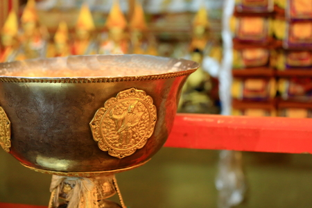 sutra: Tibetan buddhist brass vase with gilded roundel in the 183 pillars and 1850 m2 Sutra Hall of the Coqen Hall building in the Drepung-Rice Heap monastery of the Gelugpa-Yellow Hat order. Foot of mt.Ghephel-Lhasa pref.-Tibet.