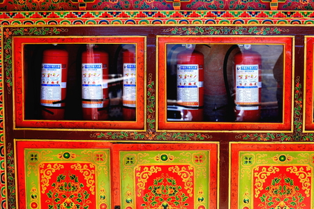 gelugpa: DREPUNG, TIBET, CHINA - OCTOBER 19: The monks keep fire extinguishers inside a red and golden painted commode with traditional drawings on October 19, 2012 in the Drepung-Rice Heap monastery of the Gelugpa-Yellow Hat order. Foot of mt.Ghephel-Lhasa pref.-