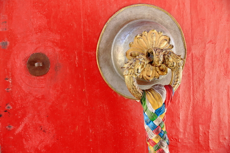 doorknob: Red wooden door-gilded brass doorknob with colorist fabric braid hanging. Kelsang Phodrang-Old-Summer Palace of the Norbulingka-Jewelled Park complex-Lhasa-Tibet.