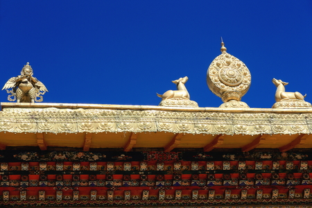 flanked: Gilded brass dharmachakra of law wheel flanked by deers and garuda atop the roof ot the Takten Mingyur Phodrang-Eternally Unchanging-New Summer Palace of the Norbulingka complex. Lhasa-Tibet A.R.-China.
