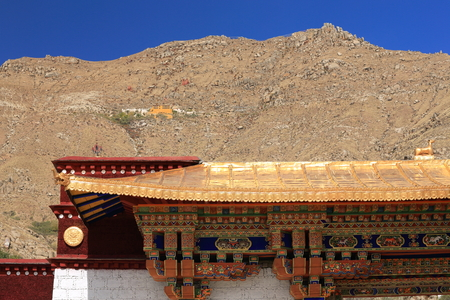 lintel: The Sera Utse hermitage-part of the 1419 AD.founded Sera-Wild Roses buddhist monastery of the Gelugpa-Yellow Hat order on the slope of Pubuchok mountain seen over a gilded roofed-painted lintel gate. Lhasa pref.-Tibet A.R.-China.
