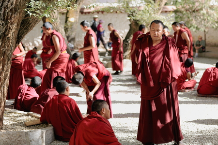 SERA, TIBET, CHINA - OCTOBER 19: Monks at debate on doctrine-part of learning process for better comprehension of buddhist philosophy. Sera-Wild Roses monastery of the Gelugpa-Yellow Hat order on the slope of Pubuchok mountain. Lhasa pref.-Tibet A.R.-Chin