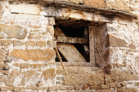 Wooden frame of ruined window with unnailed boards on the stone wall of the 1416 AD.founded Drepung monastery of the Gelugpa-Yellow Hat order at the foot of mount Ghephel. Lhasa pref.-Tibet A.R.-China.