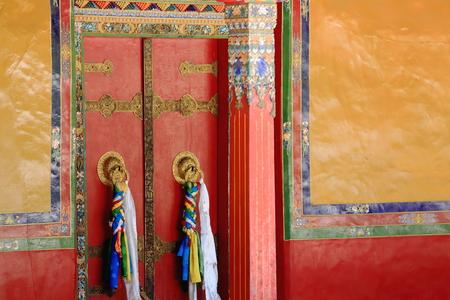 gelugpa: Red double door-black and gold decoration batten-colorist doorframe-gilded doorknobs-tibetan colored fabrics hanging-red and pumpkin color painted wall. Drepung-Rice Heap monast.of Gelugpa-Yellow Hat order. Foot of mt.Ghephel-Lhasa pref.-Tibet