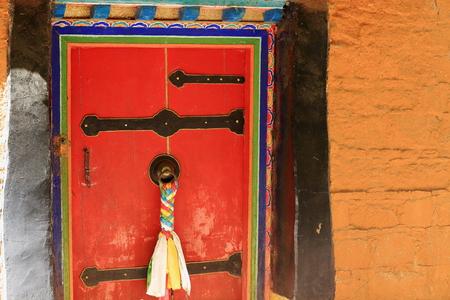 gelugpa: Red double door-black decoration battens-colorist doorframe-black doorknob-tibetan colored fabrics hanging-pumpkin color painted wall. Drepung-Rice Heap monast.of Gelugpa-Yellow Hat order. Foot of mt.Ghephel-Lhasa pref.-Tibet