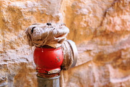 gelugpa: Red painted hydrant beside stone wall of building in the Gelugpa-Yellow Hat buddhist order Sera-Wild Roses gonpa-monastery. Lhasa pref.-Tibet A.R.-China. Stock Photo