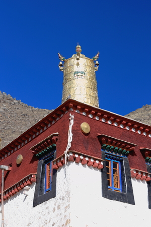 Gilded dhvaja-victory banner on rooftop of white and red stone wall-building in the 1419 AD.founded Sera-Wild Roses buddhist monastery of the Gelugpa-Yellow Hat order on the slope of Pubuchok mountain. Lhasa pref.-Tibet A.R.-China. Stock Photo