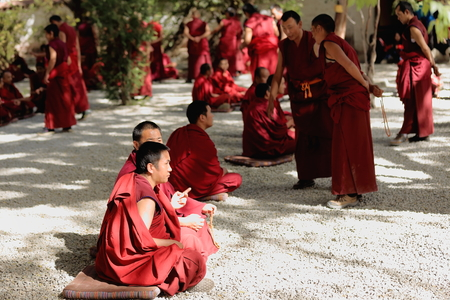 SERA, TIBET, CHINA - OCTOBER 19: Monks debate on doctrine-part of learning process for better comprehension of philosophy. Sera-Wild Roses monastery of the Gelugpa-Yellow Hat order on the slope of Pubuchok mountain. Lhasa pref.-Tibet A.R.-China.