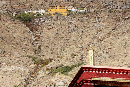 lamaism: Sera utse-hermitage high on the mountain seen over red building-dhvaja on rooftop in the Sera-Wild Roses gonpa-monast.of Gelugpa-Yellow Hat order. Pubuchok mt.slope-Lhasa pref.-Tibet-China. Stock Photo