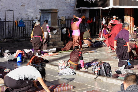 LHASA, TIBET, CHINA - OCTOBER 19: Tibetan faithfuls pray and prostrate in Barkhor square at the W.entrance to the 25000m2 Jokhang-House of Buddha temple on October 19, 2012. Lhasa-Tibet. Editorial