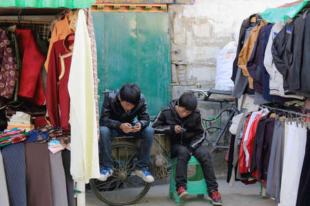 vestment: LHASA, TIBET, CHINA - OCTOBER 19: Non-tibetan han people youngsters play with e-game devices in the rear part of a street shop on the Kora-cirrcumambulation circuit on October 19, 2012. Lhasa city and pref.-Tibet A.R.-China.