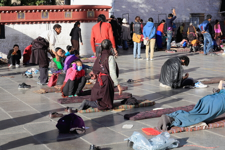 orison: LHASA, TIBET, CHINA - OCTOBER 19: Tibetan faithfuls pray and prostrate in Barkhor square at the W.entrance to the 25000m2 Jokhang-House of Buddha temple on October 19, 2012. Lhasa-Tibet. Editorial