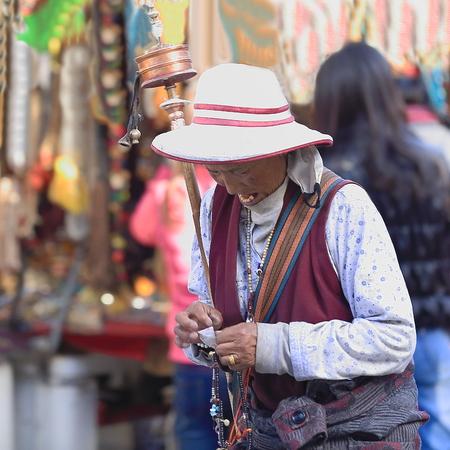 fervor: LHASA, TIBET, CHINA - OCTOBER 19: Tibetan buddhist devotee does the Kora-clockwise circumambulation around the Jokhang-House of Buddha temple on October 19, 2012 in Lhasa-Tibet A.R.-China.