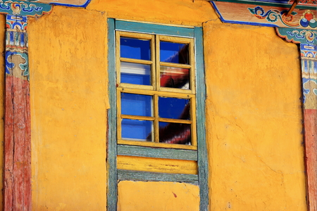 sash: Yellow-blue wooden sash window showing buddhist decorative elements in the 642 AD.founded-25000 m2 Jokhang-House of Buddha temple. Lhasa-Tibet.