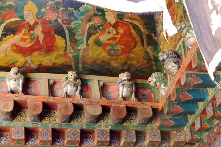 frieze: Wall frescoes with lamas and carved snow lions on wooden frieze in the Jokhang-House of Buddha temple. Lhasa-Tibet.