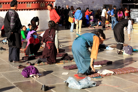 orison: LHASA, TIBET, CHINA - OCTOBER 19: Tibetan devotees pray and prostrate in Barkhor square at the W.entrance to the Jokhang-House of Buddha temple on October 19, 2012. Lhasa-Tibet.