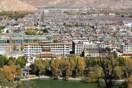 View over Lhasa city and Zongjiao Lukang park to the N.of the Potala with its Potrang Karpo and MarpoWhite and Red palaces on Marpo RiRed Hill rising 300 ms.over LhasaTibet.