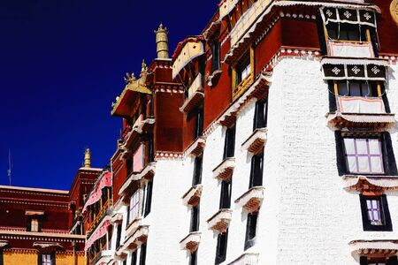 whitewashed: Whitewashed wallsgilded dhvajas. With the Potala palace Potrang Karpo and MarpoRed and White palaces to the E.and W.at 3700 ms.high on Marpo RiRed Hill 300 ms.over the valley. LhasaTibet.