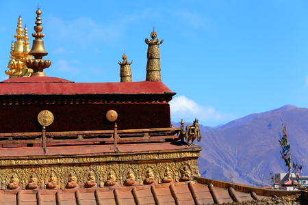 buddhist temple roof: Gilded dhvajas or victory bannersroundelsfrieze and lotus flowers on the rooftop of  the AD.642 founded25000 m2 JokhangHouse of Buddha temple. LhasaTibet.