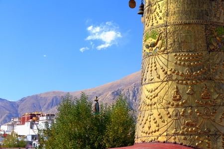 Gilded dhvajavictory banner and Potala on the background. Rooftop of  the AD.642 founded25000 m2 JokhangHouse of Buddha temple. LhasaTibet. photo