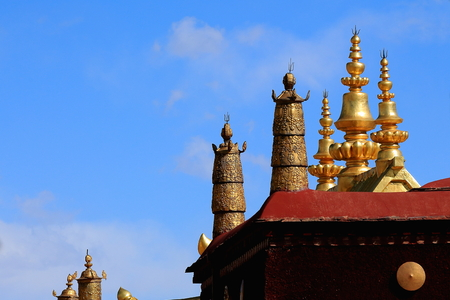 clockwise: Gilded dhvajasvictory banners and lotus flowers on the rooftop of  the AD.642 founded25000 m2 JokhangHouse of Buddha temple. LhasaTibet.