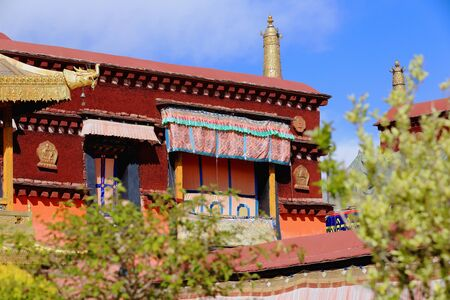clockwise: Gilded roofs and decoration dhvaja or victory bannermakara or crocodileroundel atop red roof of building in the courtyard of the AD.642 founded25000 m2 JokhangHouse of Buddha temple. LhasaTibet.