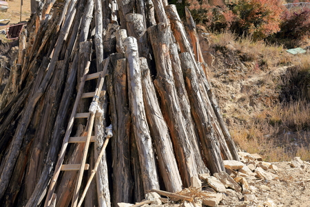 orison: Heap of wooden logs with ladder piled at the foot of the mountain slope in which stands the Drak Yerpa monasterycomplex of more than 80 meditation caves at 4885 ms.alt. Lhasa pref.Tibet A.R.China. Stock Photo