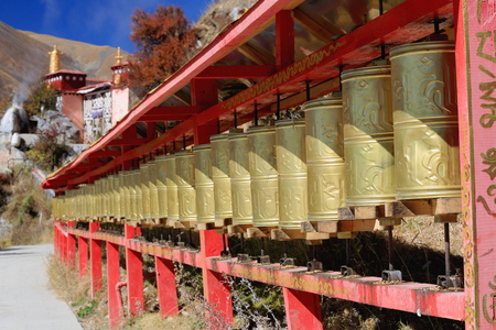 orison: Row of big brass prayer wheels hanging on a red wooden frame on the way up the mountain slope to the main buildings of the 4885 ms.high Drak Yerpa monasterycomplex of more than 80 meditation cavesLhasa pref.Tibet A.R.China.