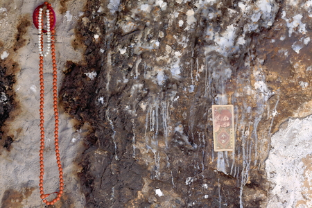 Cave wall with religious offerings bead necklacebank notetraces of candlewax. In the 4885 ms.alt.Drak Yerpa monasterycomplex of more than 80 buddhist meditation caves. Lhasa pref.Tibet. photo
