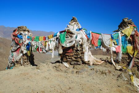 orison: Five colored buddhist prayer flags hanging from cairnsstacked stones seemingly of slate half way up to the 4793 ms.high Kamba Lapass. LhokaShannan pref.Tibet. Stock Photo