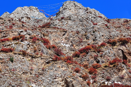buddhist meditation: Frayed buddhist prayer flags hanging on the mountain slope over the Drak Yerpa monasterycomplex of more than 80 buddhist meditation caves at 4885 ms.alt. Lhasa pref.Tiber A.R.China. Stock Photo