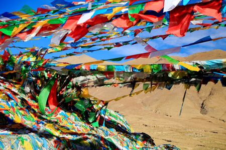 orison: Buddhist prayer flags under blue sky waving in the wind in the Nachan Lapass at 4500 ms.high over the KyichuLhasa river valley to the NE.from Lhasa Lhasa pref.Tibet A.R.China. Stock Photo
