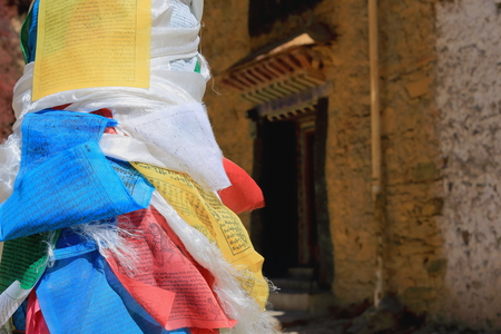 orison: Pole post wrapped in five colored buddhist prayer flags. Way down from the main buildings of Drak Yerpa monasterycomplex of more than 80 meditation caves. Lhasa pref.Tibet.