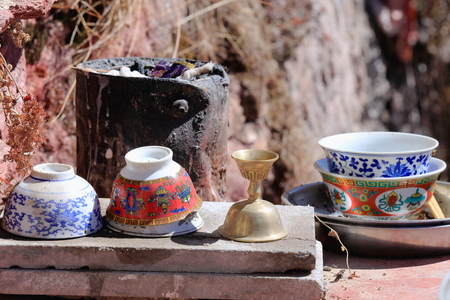 Set of ceramic cups and bowls decorated with ashtamangalabuddhist auspicious symbols along with brass candlestick and paint bucket as improvised furnace. Drak Yerpa monast.complex of  than 80 buddhist meditation caves. Lhasa pref.Tibet. photo