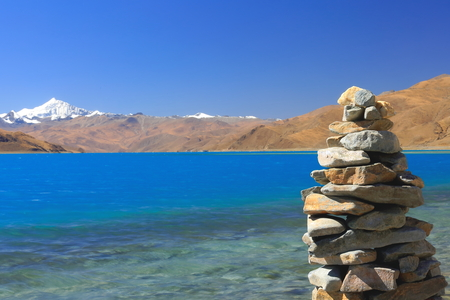 Cairnstone stack on the shore of the 638 km2130 km.E'W70 km.N'S wide250 long bank4441 ms.highturquoise colored Yamdrok TsoUpper Pasture lake and 7206 ms.high mt.Nojin Kangsang on the background. Lhoka or Shannan pref.Tibet. Foto de archivo