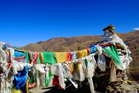 orison: Five colored buddhist prayer flags hanging from cairnsstacked stones seemingly of slate half way up to the 4793 ms.high Kamba Lapass. Lhoka or Shannan pref.Tibet.