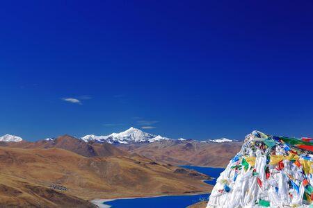 Prayer flags on Kamba Lapass overlooking the 638 km2130 km.EW70 km.NS wide250 long bank4441 ms.highturquoise colored Yamdrok TsoUpper Pasture lake and 7206 ms.high mt.Nojin Kangsang. Lhoka or Shannan pref.Tibet.