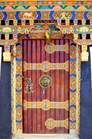 lintel: Profusely decoratedtraditional tibetan stylewooden door in the old area of the town. Gyantse city and countyShigatse pref.Tibet. Editorial