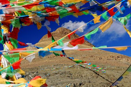 red mountain open space: Buddhist prayer flags hanging from an unidentified peak over the 4200 ms.high Smira La-mountain pass overlooking the turquoise color Manla Reservoir on the Nyang river. Gyantse county-Shigatse pref.-Tibet.